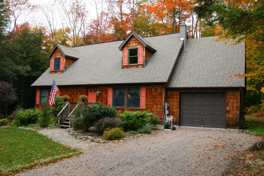 Cape with cedar shakes, attached one-car garage and deco dormers.