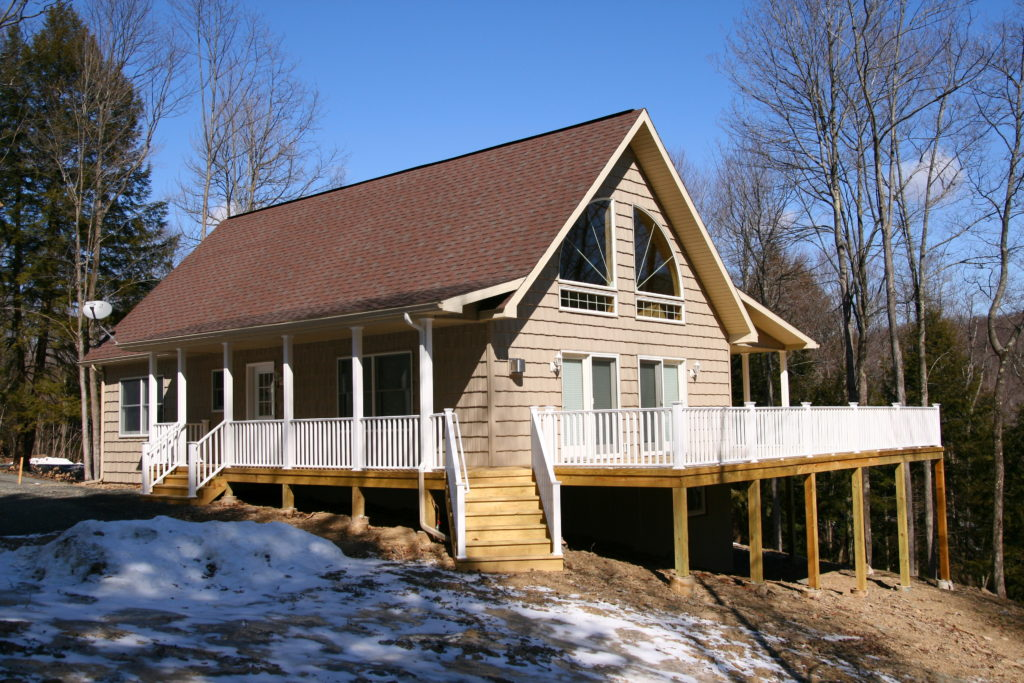 Cape Chalet with wrap-around porch/deck, and shed roof porches.