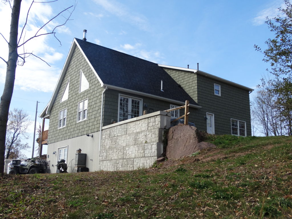 Cape chalet with vinyl shakes and shed dormer